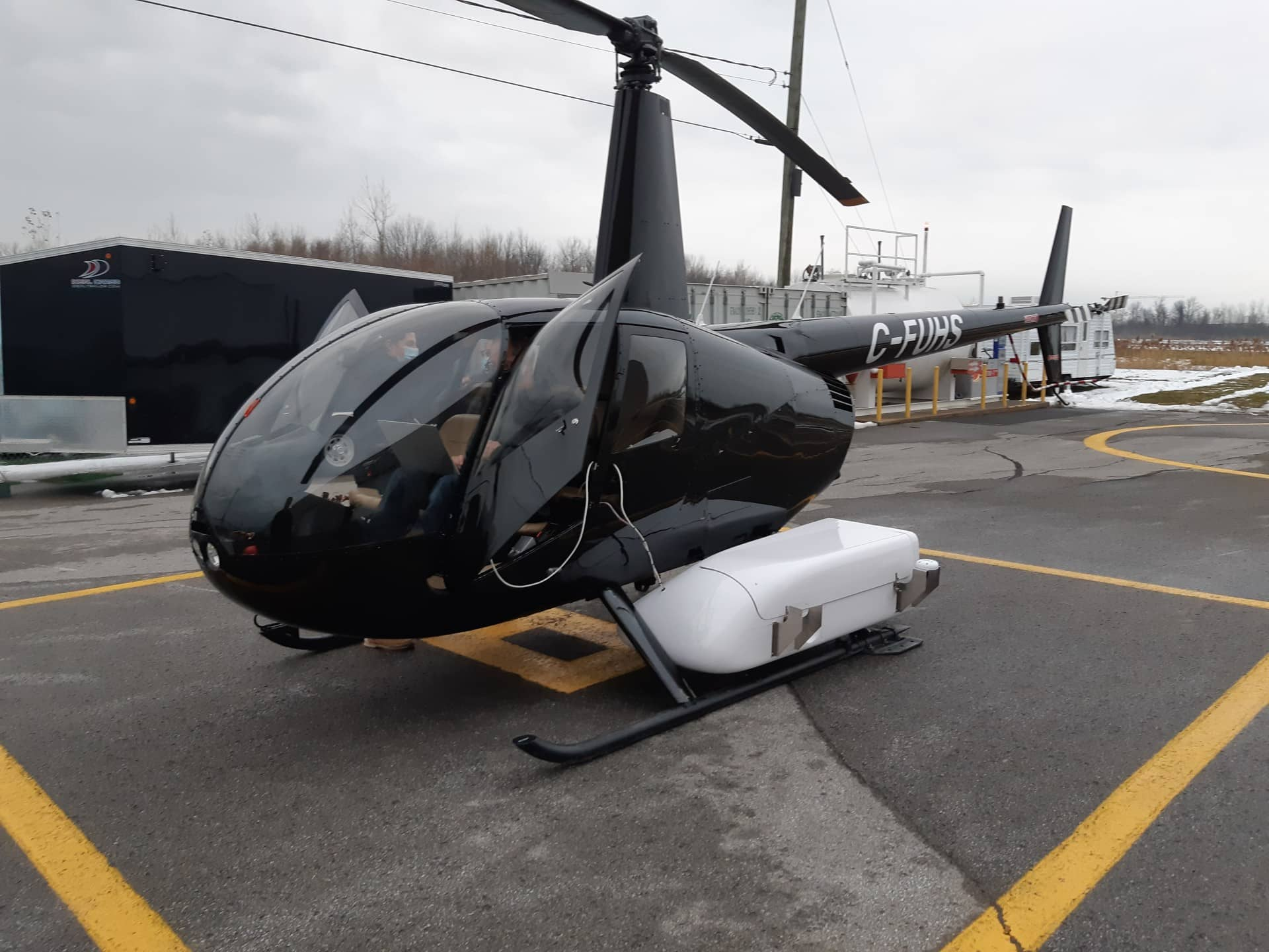 A black helicopter pod about to go flying with 2 persons