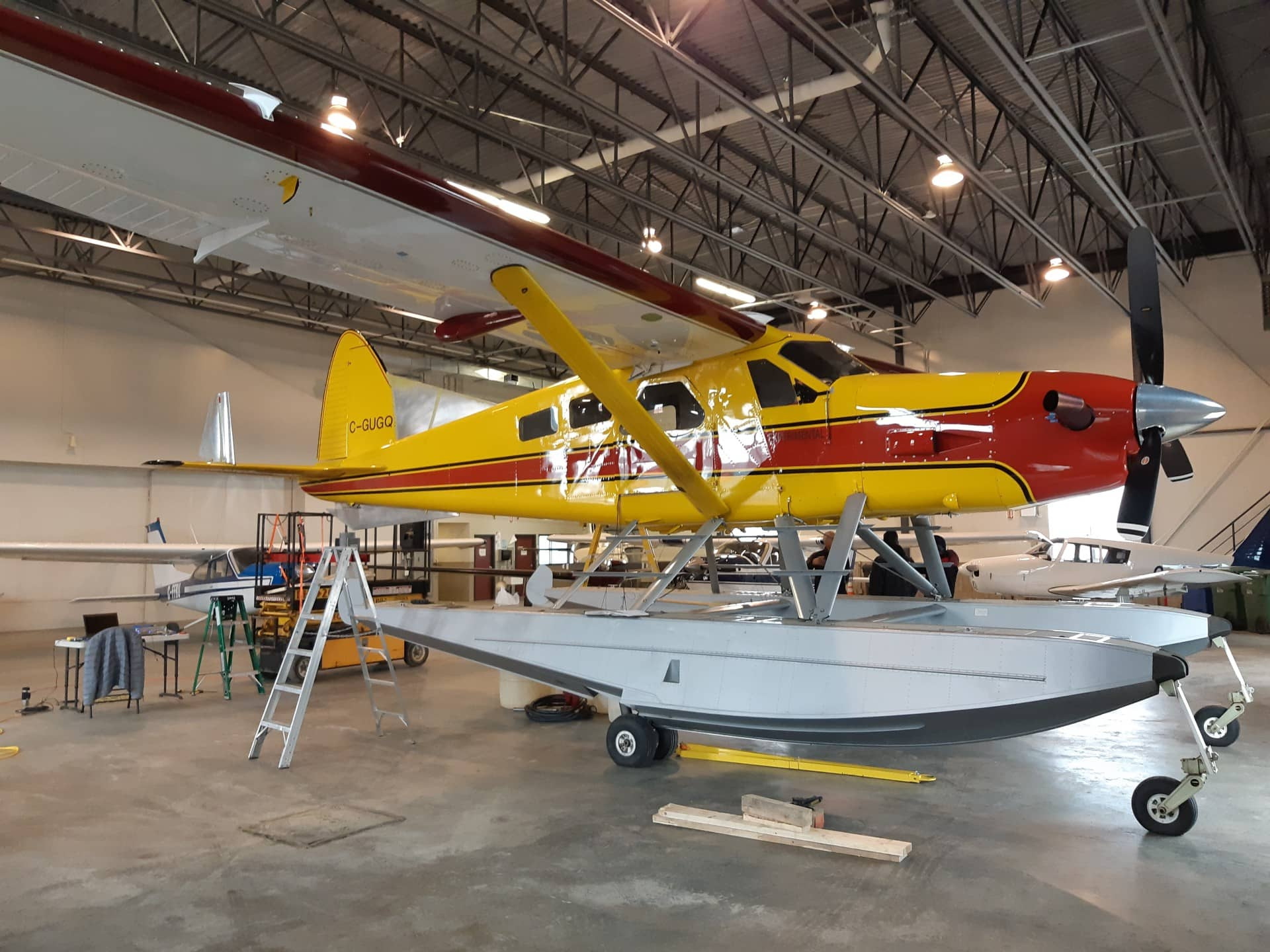 A yellow and red plane inside a garage